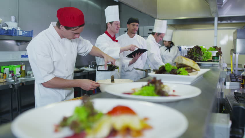 Professional chefs in a restaurant or hotel kitchen. They are looking at a digital tablet and organizing their menu and work schedule. | Shutterstock HD Video #4448888