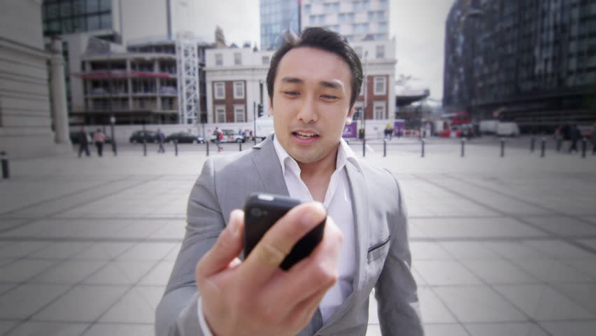 Businessman walking with cell phone outdoors in the city. Shot on steadycam with RED Epic digital cinema camera.