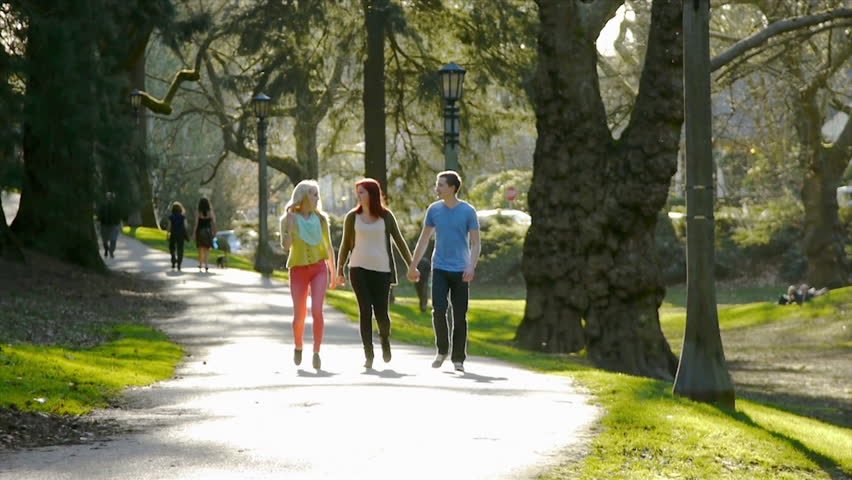 3 Happy Friends Walk Down Path Through Park Toward Camera