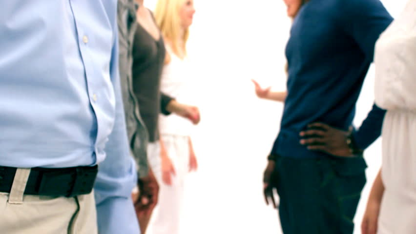 Diverse group of young adults walking past camera and shaking hands on a white background