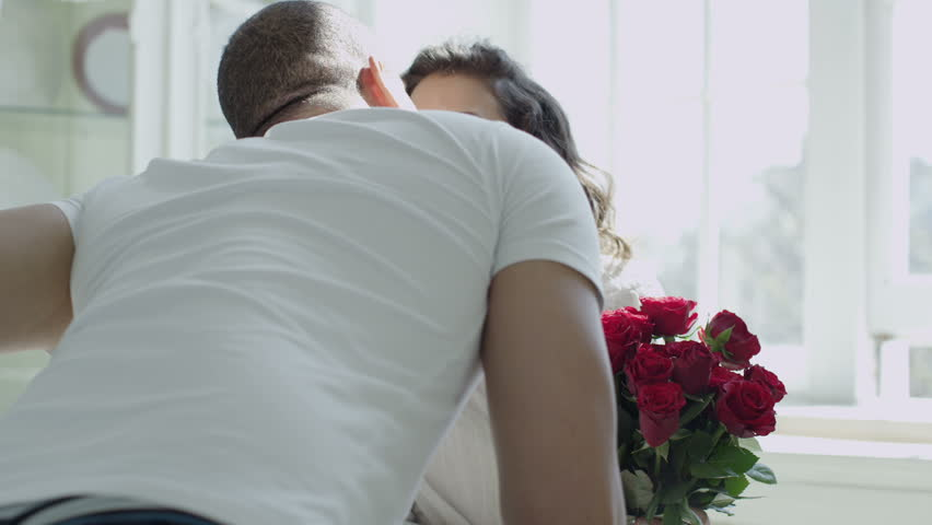 Romantic and affectionate young mixed race couple relaxing together at home. The man has given his partner a bouquet of fresh red roses. In slow motion.