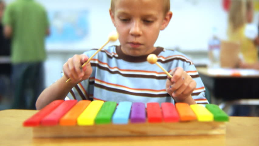 Young boy playing xylophone at school