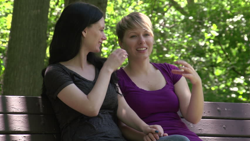 Happy female couple at a park, laughing