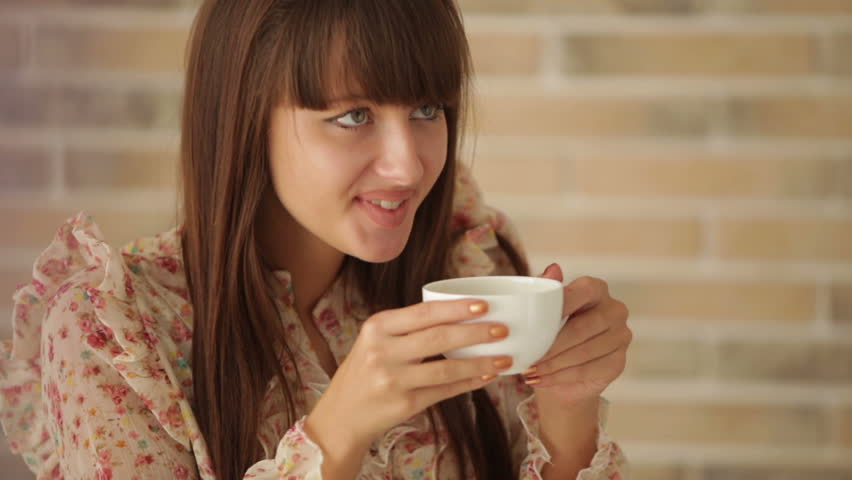 Young woman sitting at cafe smiling and drinking coffee