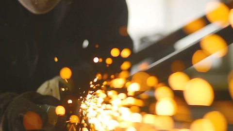 Worker grinding metal construction with a circular saw