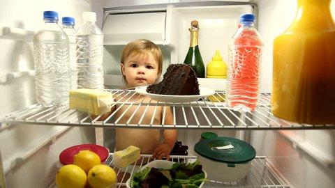 Baby eating chocolate cake in refrigerator