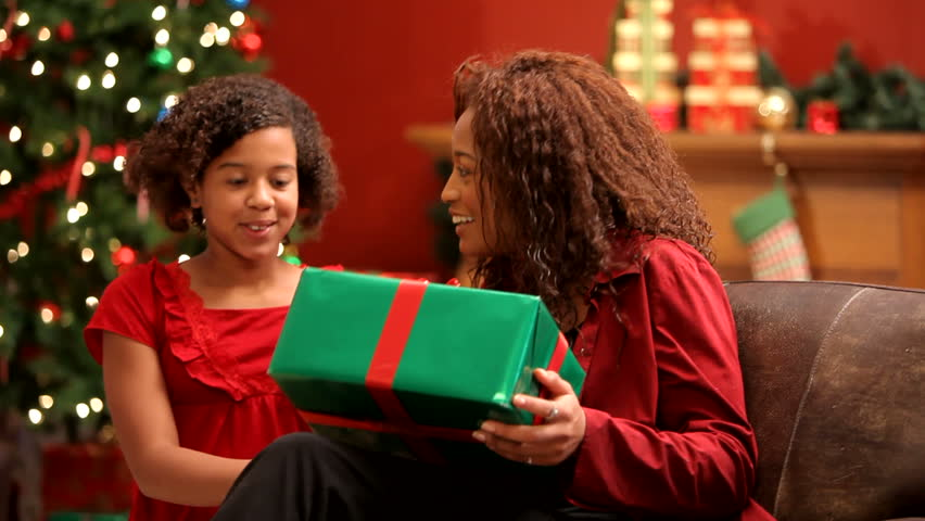 Child giving Christmas gift to mother