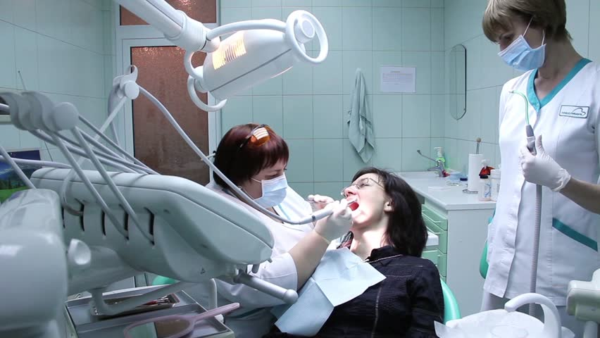 Dentist Working With A Little Patient, Assistant Helping Him Stock ...