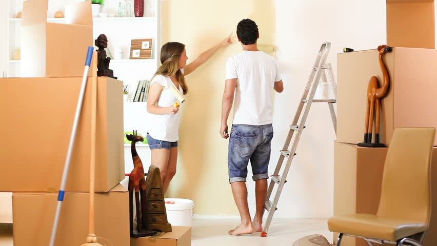 Young Couple Decorate Their New Apartment Moving In New Home Man Are Paint The