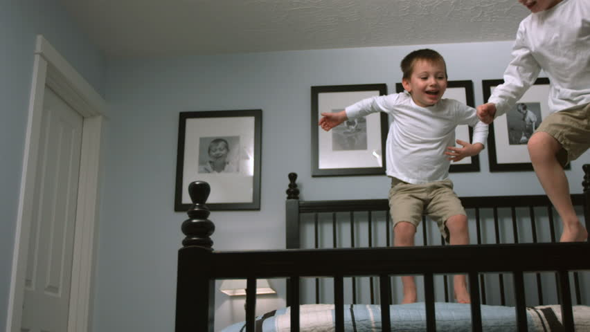 Boys jump on bed, slow motion