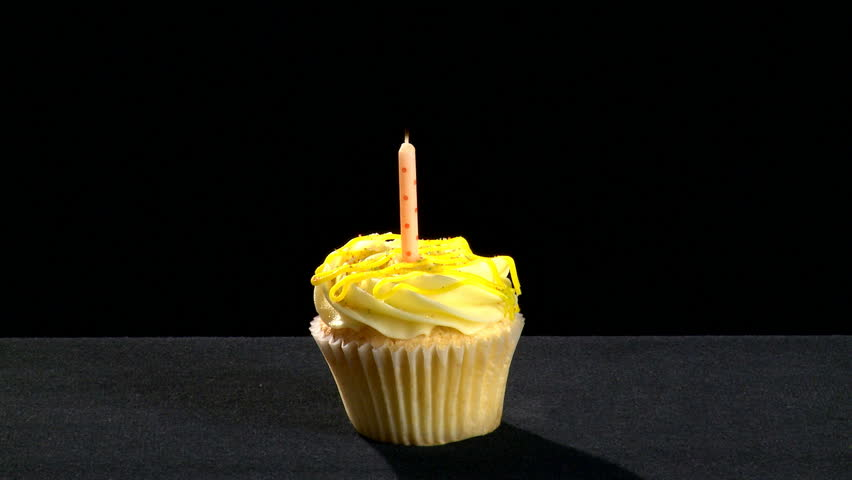 A vanilla cupcake on a black background. The candle is first lit and then blown out. Ideal to represent birthdays, anniversaries, celebrations and parties.