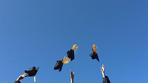 Tossing graduation caps, slow motion