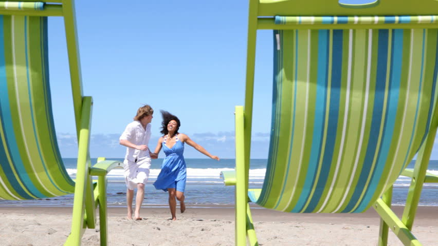 Couple running on beach to chairs
