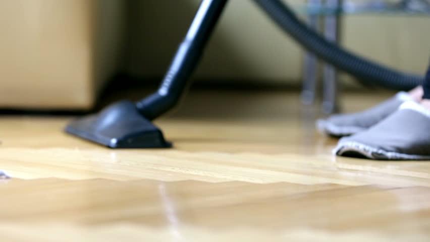 Vacuuming debris on floor parquet. Woman doing cleaning work in house, vacuuming floor in house.