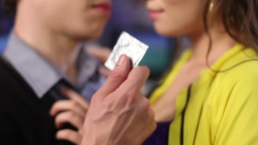 Man offers woman condom she opens it up tearing the envelope. Safe love no risk