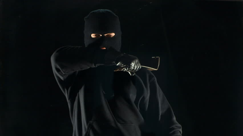 Masked robber breaking window with crowbar, slow motion