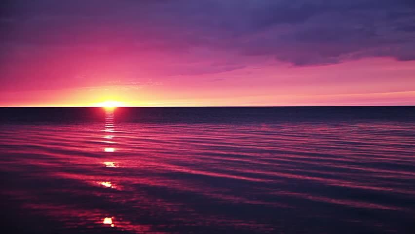 Calm ocean. Overcast. On the horizon - a clear sky and sunset
