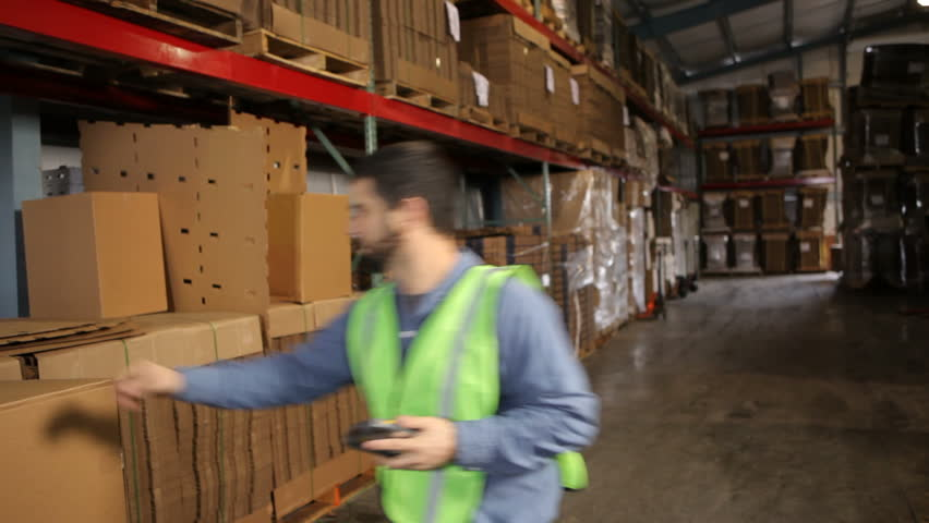 Man in shipping warehouse scans labels on boxes