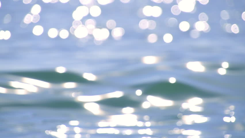 Sparkling fresh wavy water is shining on a sunny summer day in slow motion, abstract blurry background at the seaside