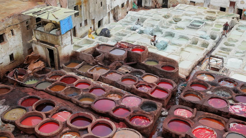 Close overhead view of men stacking dyed garments at a leather tannery in a residential neighborhood in Fez, Morocco