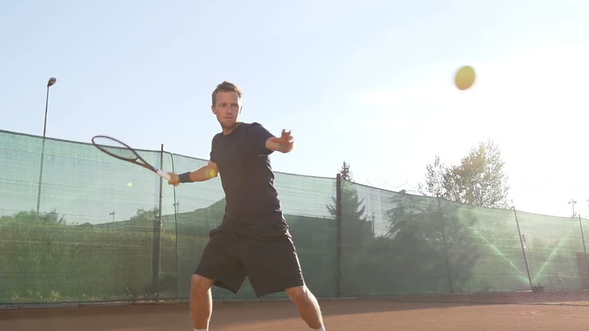 Slow Motion Shot Of A Professional Tennis Player Hitting Forehand With Tennis Racket On Clay Court