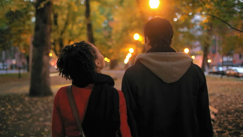 A young couple walk through a city park together heading away from the camera. Medium shot.