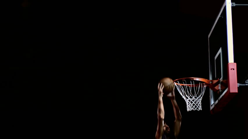 A basketball floats through the air in slow motion and hits the a basketball player dunks the ball in the shadows hd stock video clip voltagebd Images