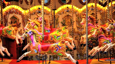 Empty fairground carousel moving with colorful wooden horses, London, United Kingdom