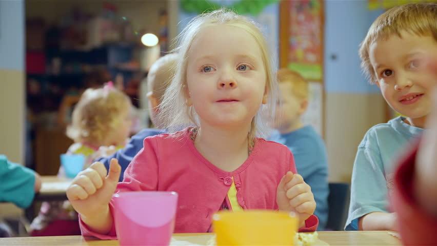 A cute little girl eats popcorn in school
