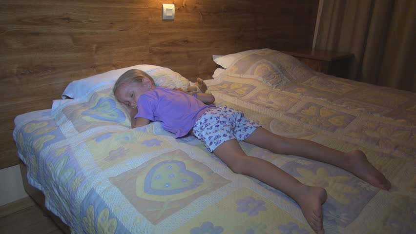 Above told little girl sleeping in bed feet
