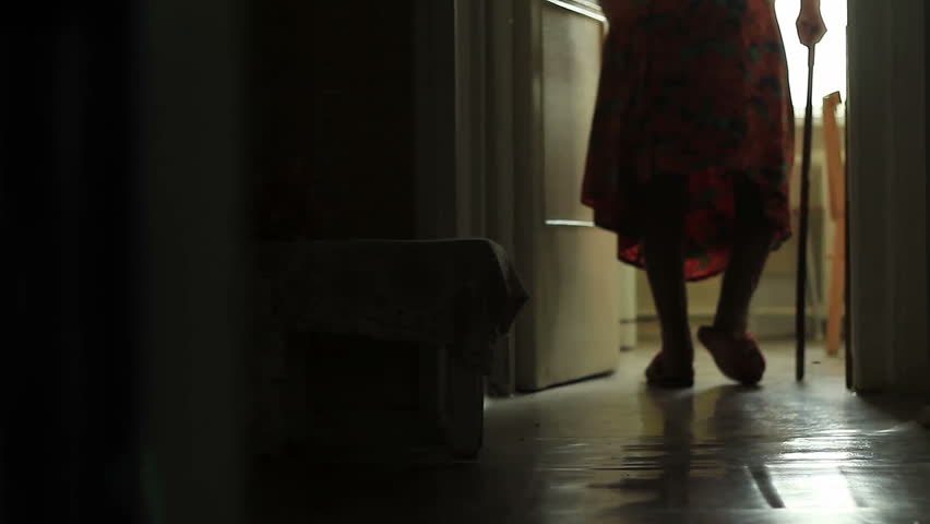 Silhouette of an old woman walking with a cane at home