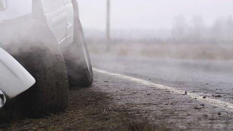 Smoke billows from a recently crashed pickup truck. Medium shot.