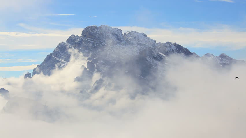 Black birds fly and wheel around the rocky peak of a Dolomite Mountain above the clouds at Misurina nearr Cortinad di Ampezzo in the Italian Alps, Italy | Shutterstock HD Video #4681274