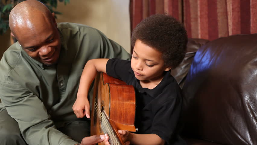 Father teaches his son to play guitar