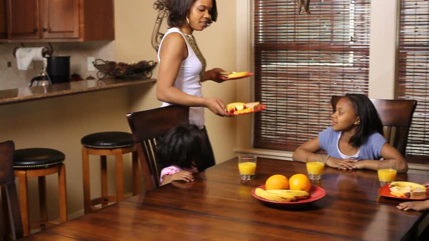 Portrait of African American mother serving her kids food