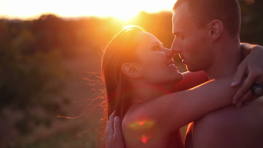 Attractive couple kiss passionately during sunset. Medium shot.