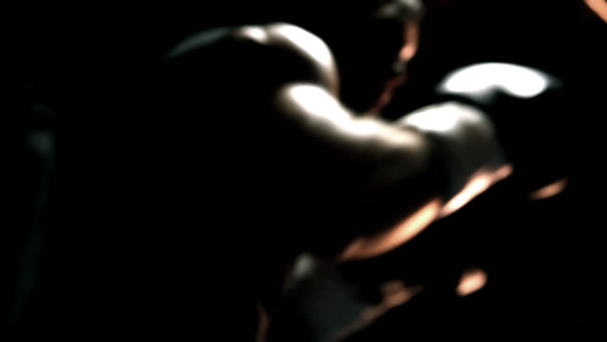 Muscular athlete practices boxing on a punching bag. Close up shot.