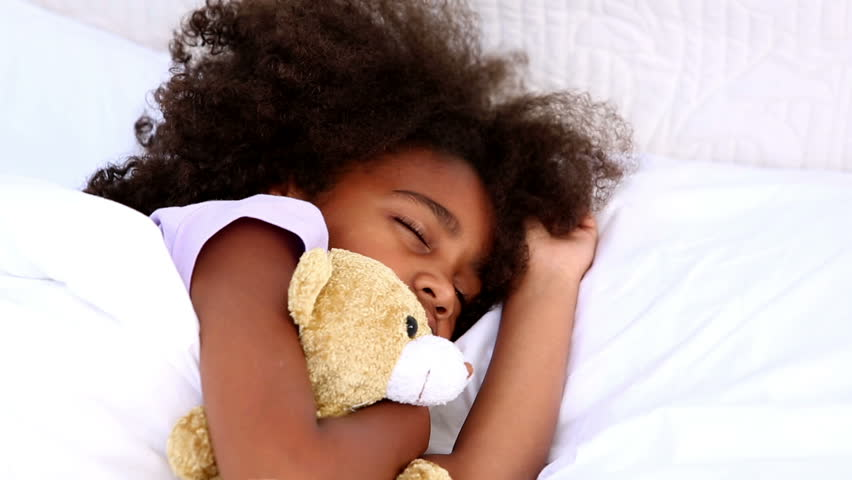 Little girl sleeping with teddy bear in bed at home