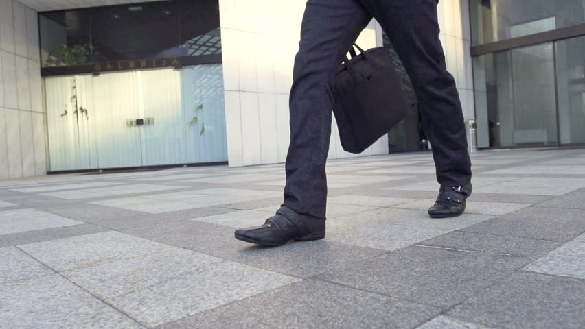 Slow Motion Shot Of A Male Legs Walking Through Business Area. Casually Dressed