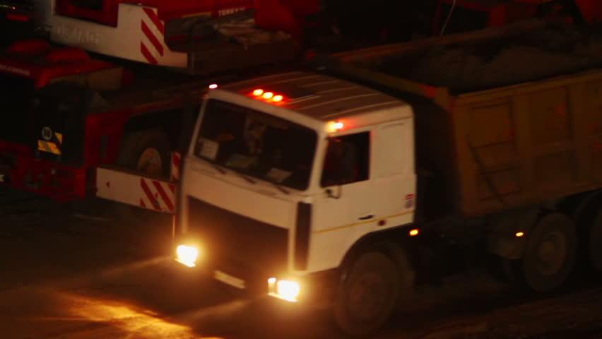 Construction yard trucks drive, working machines, night site