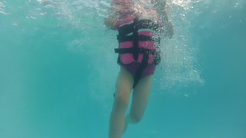 A girl jumps into a pool with a life jacket underwater shot