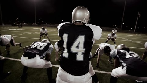 Over the shoulder view of a quarterback in the huddle and walking to the line before the snap