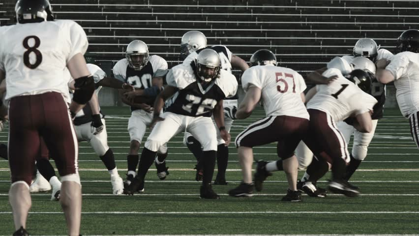 Football players run a running play from the line | Shutterstock HD Video #4706363