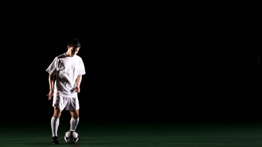 Isolated soccer player on black juggles a ball