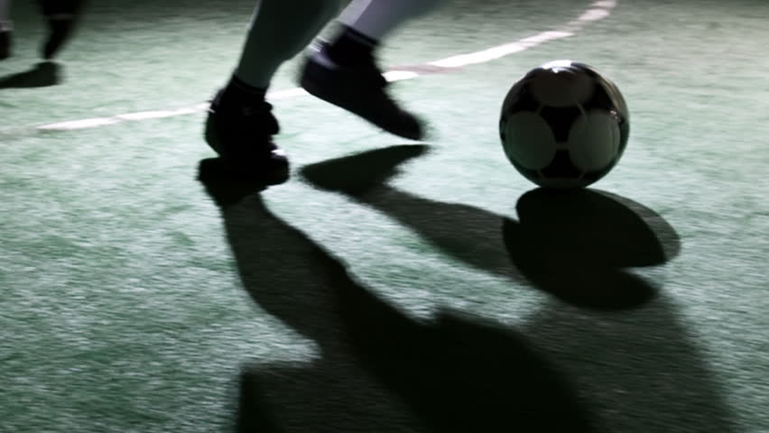 Close up of a soccer player's feet dribbling a ball and weaving through defenders
