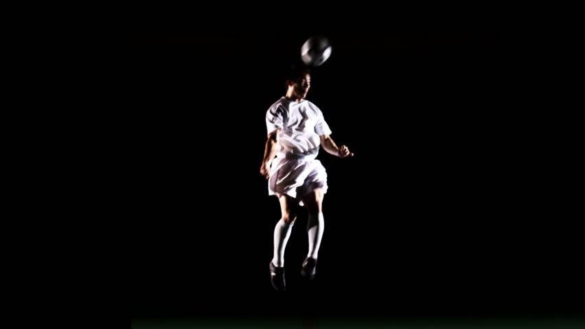 An isolated soccer player jumps up and heads the ball in the air on black