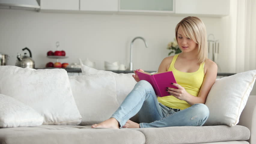 Cute girl relaxing on sofa reading book closing it and smiling at camera