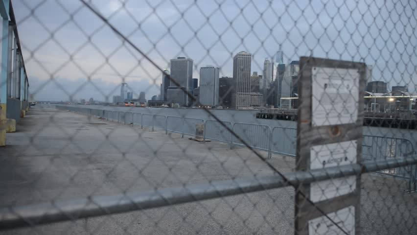 New York City Skyline filmed from Pier 9 in Dumbo with fence covering view