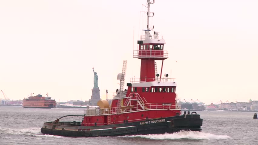 NEW YORK - CIRCA FEBRUARY 2011 - Statue of Liberty seen from Brooklyn, NY in February 2011. Boat passes in front of the camera. | Shutterstock HD Video #4740053