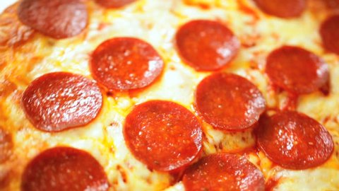 Close up of a delicious slice of home baked Pepperoni cheese pizza in slow motion